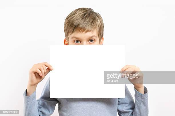 Young boy retención de hoja de papel en blanco