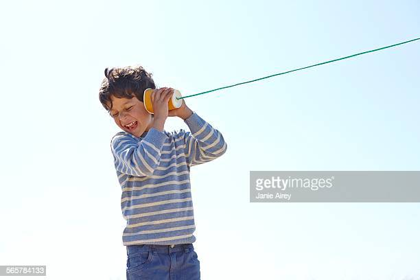 young boy, holding cup and string telephone to ear - string stock pictures, royalty-free photos & images