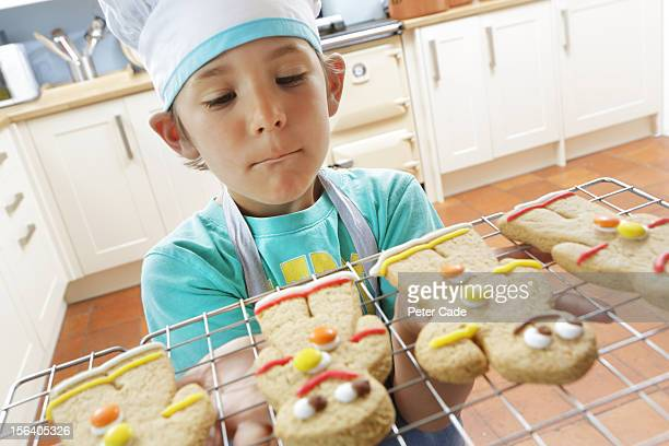 Young boy holding freshly baked gingerbread men