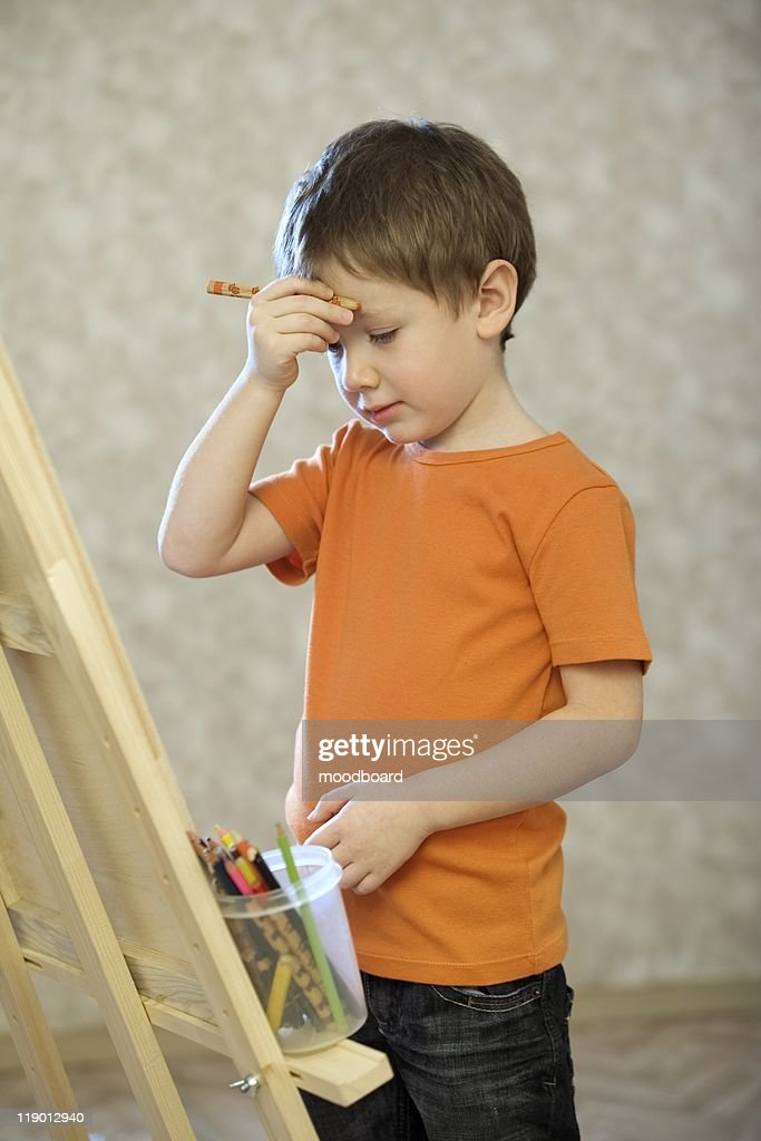 A young boy holding his hand with a pencil in up to his face, standing infront of a canvas with a pot of coloured pencils : Stock Photo