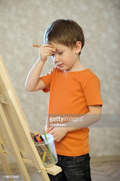 A young boy holding his hand with a pencil in up to his face, standing infront of a canvas with a pot of coloured pencils