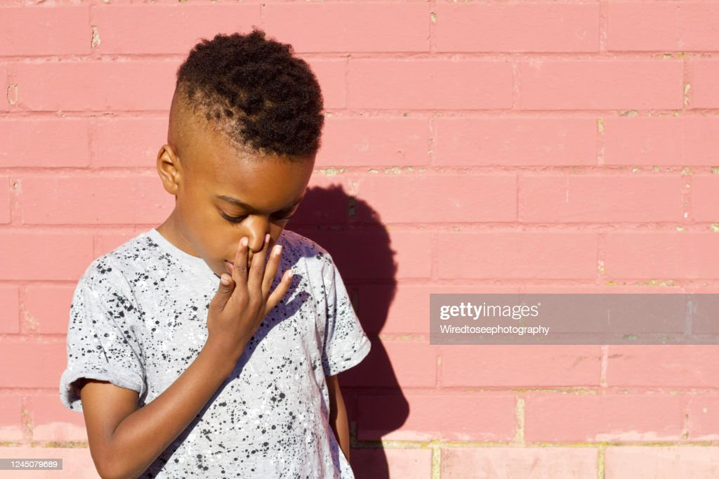 Young boy holding his nose in front of a pink wall : ストックフォト