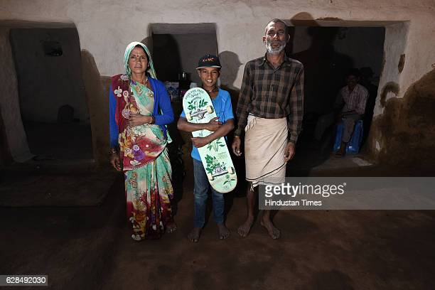 Young boy holding his skateboard with his parents poses on October 26, 2016 in Janwaar, India. Thanks to a German community activist and author...