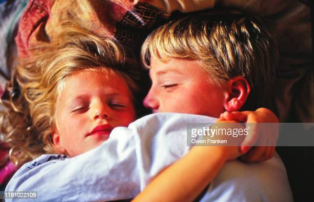 young boy holding his younger sister in his arms - image photos et images de collection