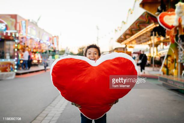 young boy holding large prize he won at fun fair - big tom stock pictures, royalty-free photos & images