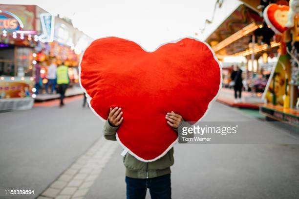 young boy holding large soft heart toy at fun fair - beating heart stock pictures, royalty-free photos & images