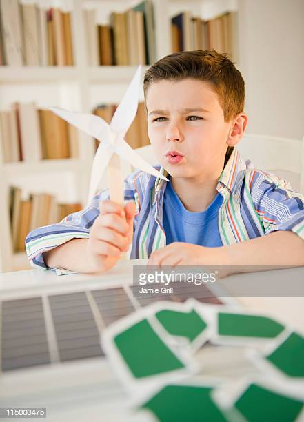 Young boy holding model of wind turbine
