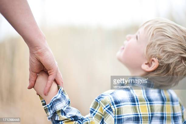 Young boy holding mom's hand