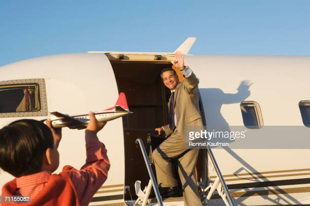 Young boy holding out an airplane as his father leaves