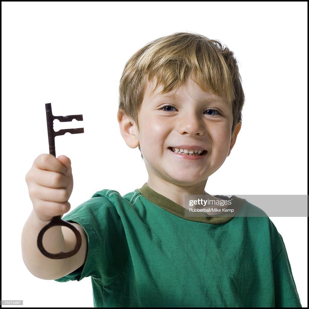Young boy holding skeleton key smiling : Stock Photo
