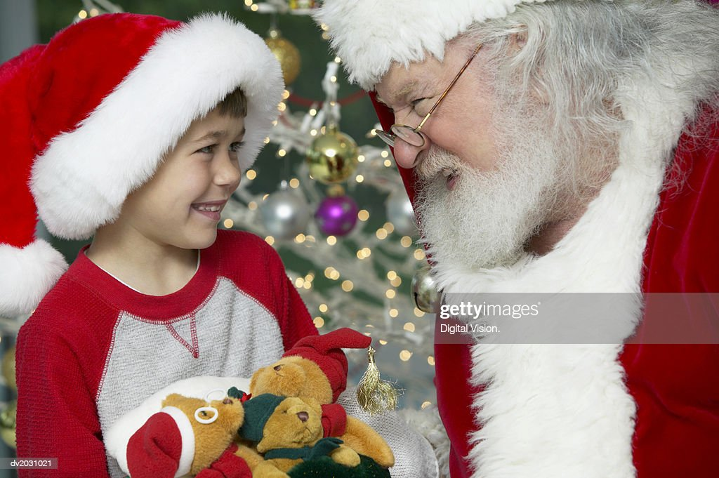 Young Boy Holding Three Teddy Bears Looking Face to Face With Santa Claus : Stock Photo