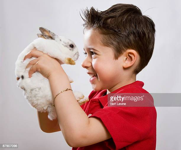 Young boy holding up a bunny in a pet shop