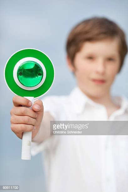 young boy holding up go sign