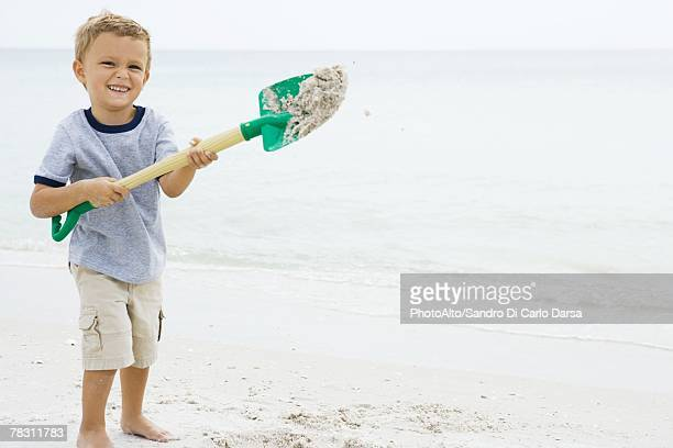 Young boy holding up shovel and throwing sand, smiling at camera