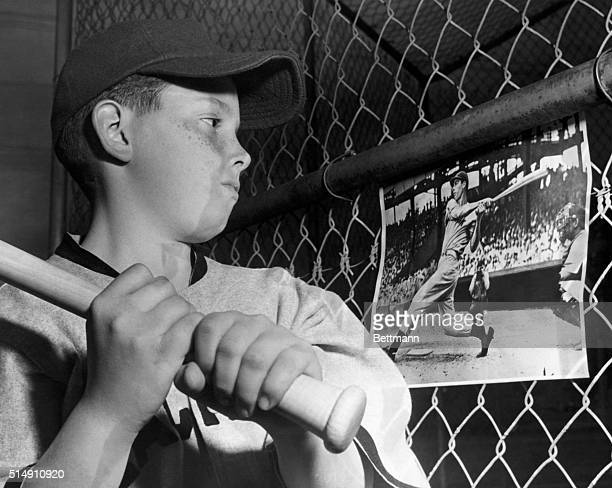 A young boy holds a baseball bat while looking at a photograph of Joe DiMaggio Undated photograph