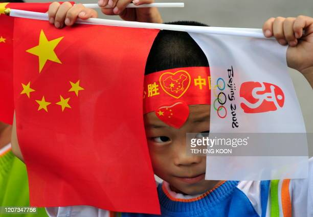 A young boy holds a Chinese flag along with the flag of the 2008 Beijing Olympic Games during the Olympic torch relay ceremony near the Tiananmen...