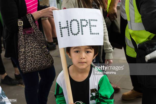 A young boy holds a flag with a word 'hope' as hundreds of people assemble outside Downing Street in central London for a protest march to the Home...