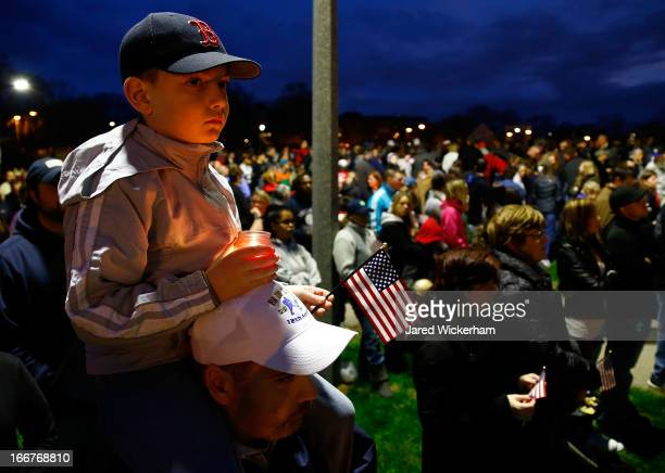 A young boy holds a lit candle and an American flag atop his father's shoulders during a vigil for eightyearold Martin Richard from Dorchester who...