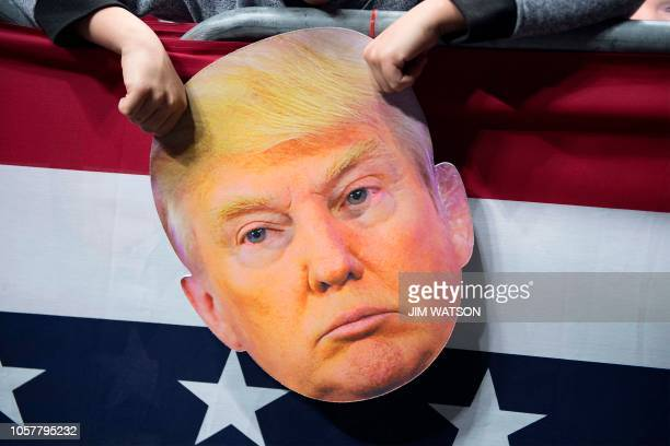 A young boy holds a mask of US President Donald Trump as Trump delivers remarks at a Make America Great Again rally in Fort Wayne Indiana on November...