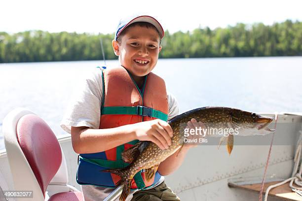 a young boy holds a northern pike in a fighing boat and smiles. - northern pike stock photos and pictures
