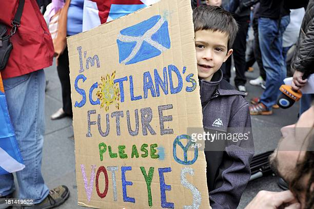 A young boy holds a placard as people gather in Edinburgh on September 21 2013 for a march and rally in support of a yes vote in the Scottish...