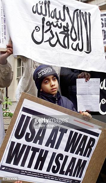 A young boy holds a placard as protesters belonging to the Al Muhajiroun chant anti US slogans and show their support to Osama Bin Laden and the...