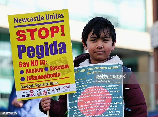 A young boy holds a placard during a countermarch against members of right wing movement Pegida taking part in a demonstration on February 28 2015 in...
