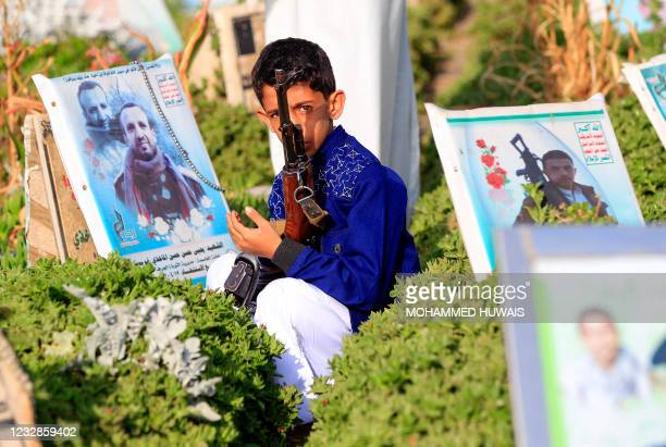 Young boy holds a rifle as he visits a grave in the capital Sanaa on May 13 as Yemenis mark the end of the holy month of Ramadan.