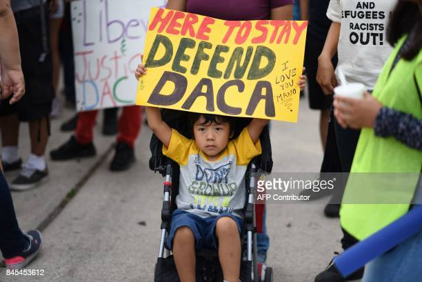 A young boy holds a sign during a protest September 10 2017 in Los Angeles California against efforts by the Trump administration to phase out DACA...