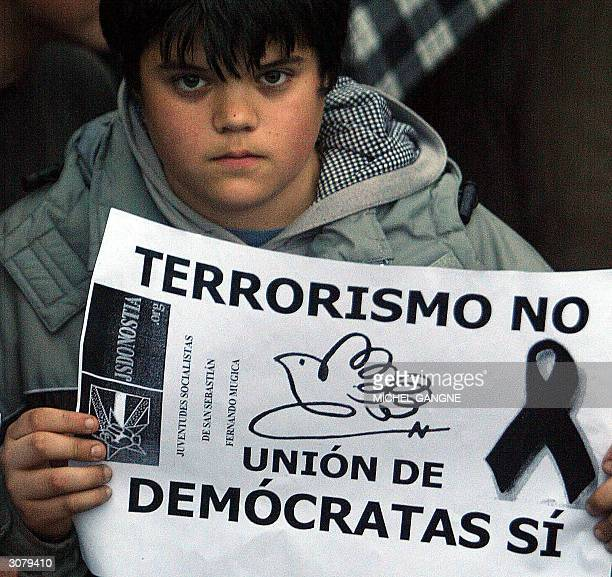 A young boy holds a sign saying 'no to terrorism yes to democracy' as he demonstrates with thousands of others in San Sebastian in solidarity with...