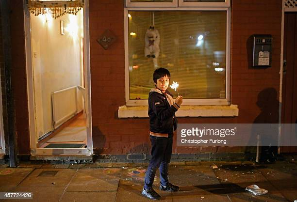 A young boy holds a sparkler outside his home as he celebrate the Hindu festival of Diwali on October 23 2014 in Leicester England Up to 35000 people...