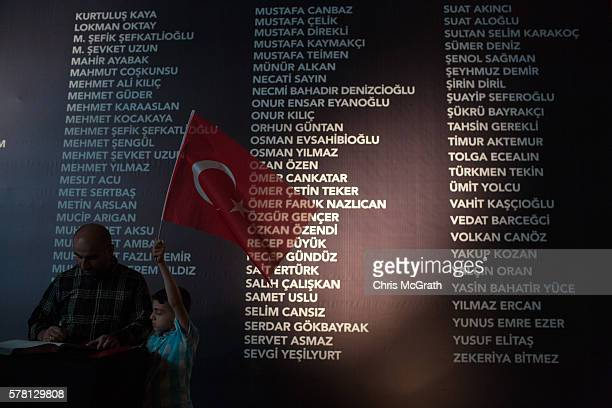 A young boy holds a Turkish flag in front of a board listing the names of people killed during the failed coup attempt at Taksim Square on July 20...
