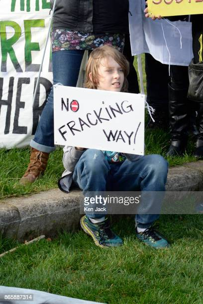 A young boy holds an antifracking poster during a demonstration outside the Scottish Parliament as MSPs prepared to debate the issue on October 24...