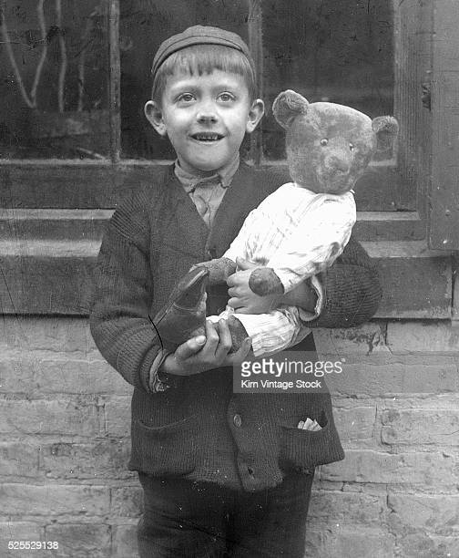 A young boy holds his teddy bear ca 1920