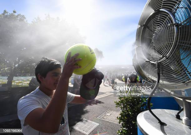 Young boy holds his tennis ball across his face as he cools down in front of a water fan during day one of the 2019 Australian Open at Melbourne Park...