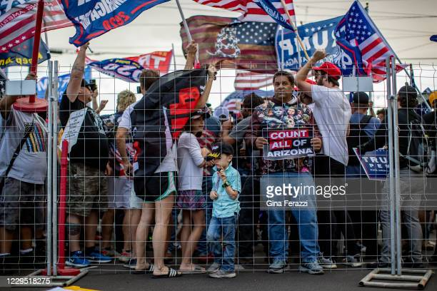 Young boy holds onto a fence as pro-Trump supporters rally to defy the election results hours after Biden was named President-elect outside the...