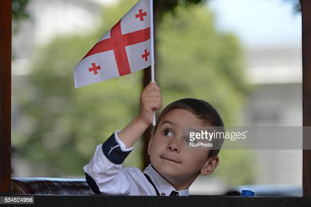 A young boy holds the national flag of Georgia inside a bus as any people of all age gathered in Tbilisi center for a popular celebrations as Georgia...