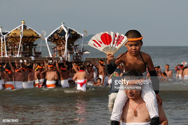 Young boy holds up a fan during the Ohara Hadaka Festival on September 23, 2008 in Isumi City, Chiba Prefecture, Japan. The Ohara Hadaka Festival is...