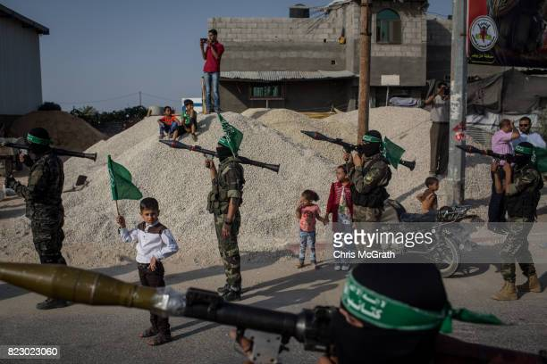 A young boy holds up a Hamas flag in between Palestinian Hamas militant during a military show in the Bani Suheila district on July 20 2017 in Gaza...