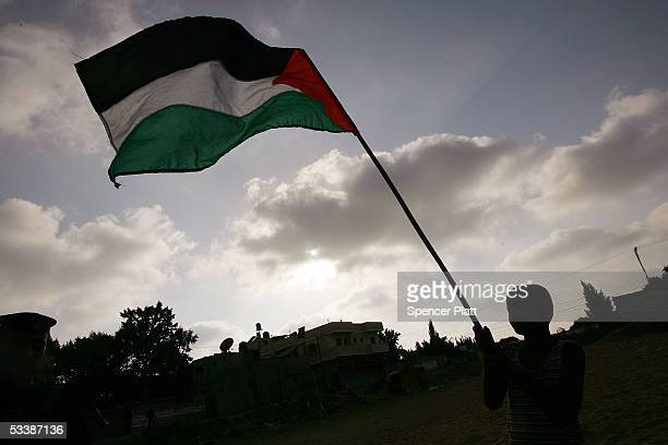 A young boy holds up a Palestinian flag as members of the Palestinian security forces set up camp near the boarder of the Kfar Darom settlement in...