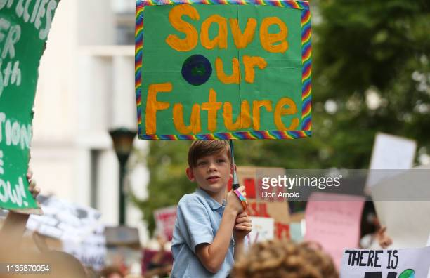 A young boy holds up a sign as he sits on his fathers shoulders during a Climate Change Awareness rally at Sydney Town Hall on March 15 2019 in...