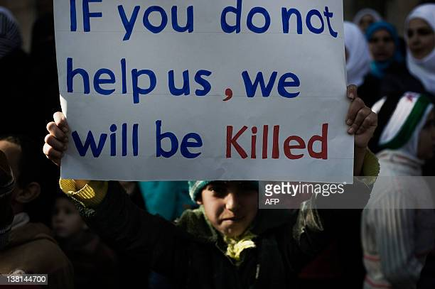 A young boy holds up a sign during an antiregime demonstration in the Syrian village of alQsair 25 km southwest of the flashpoint city Homs on...