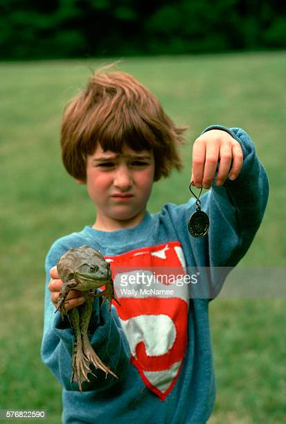 A young boy holds up his frog and the medal he won in a frog jumping contest that was part of a bicentennial celebration