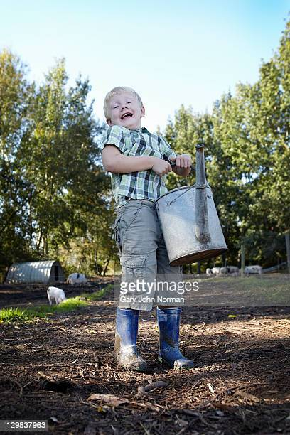 Young boy hols watering can on small holding