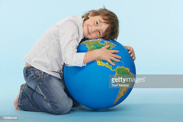 Young boy hugging a globe indoors