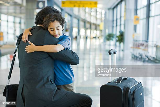 young boy hugging father in airport terminal - kid in airport stock pictures, royalty-free photos & images