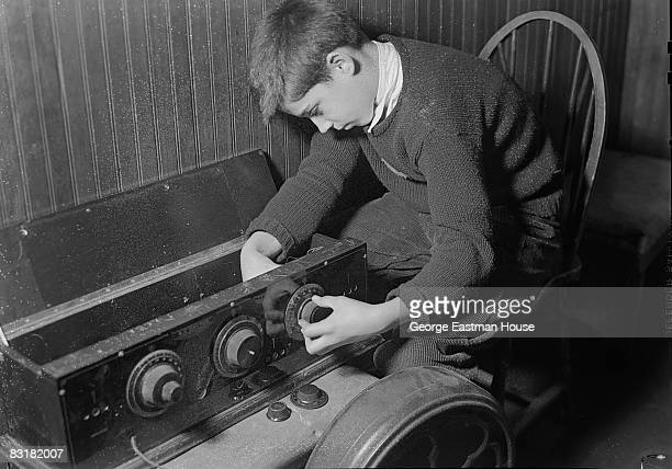 A young boy hunkers down and gets to work building out a project using what look like old radio dials United States ca1930s