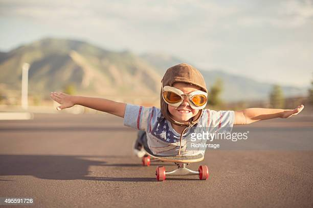 young boy imagines flying on skateboard - motivatie stockfoto's en -beelden