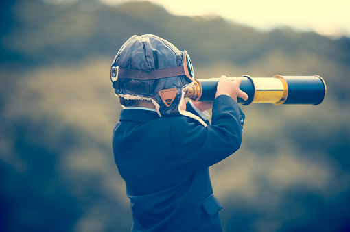 Young boy in a business suit with telescope. 473284352