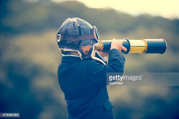 young boy in a business suit with telescope. - planning stockfoto's en -beelden